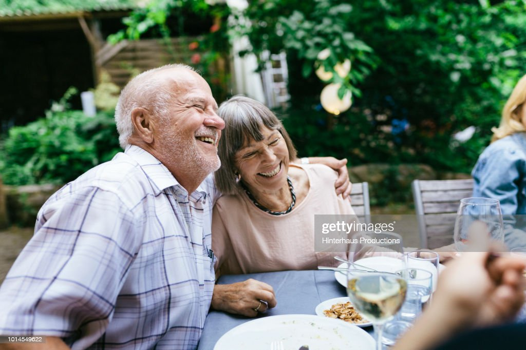 Elderly Couple Enjoying Outdoor Meal With Family : Stock Photo