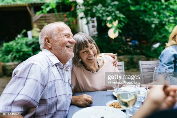 elderly couple enjoying outdoor meal with family - alter erwachsener stock-fotos und bilder