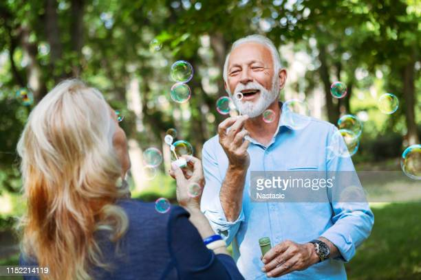 elderly couple enjoying themselves blowing bubbles - gerontology stock pictures, royalty-free photos & images
