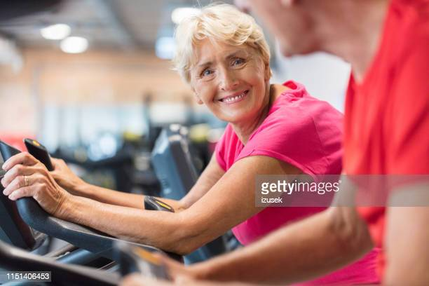 elderly couple exercising on cycling machines in gym - cardiovascular exercise stock pictures, royalty-free photos & images