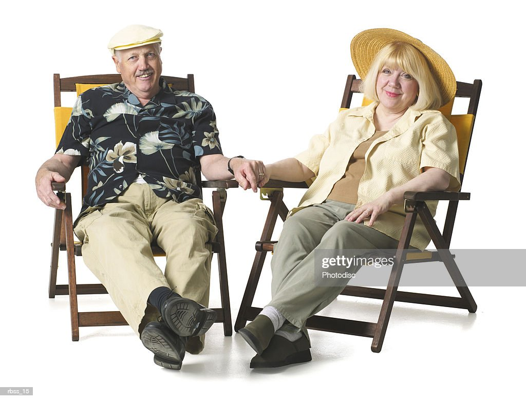 Elderly couple happily lounge in patio chairs. : Foto de stock