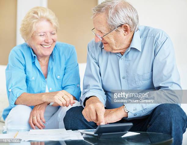 Elderly couple happy over the results after calculating their expenses