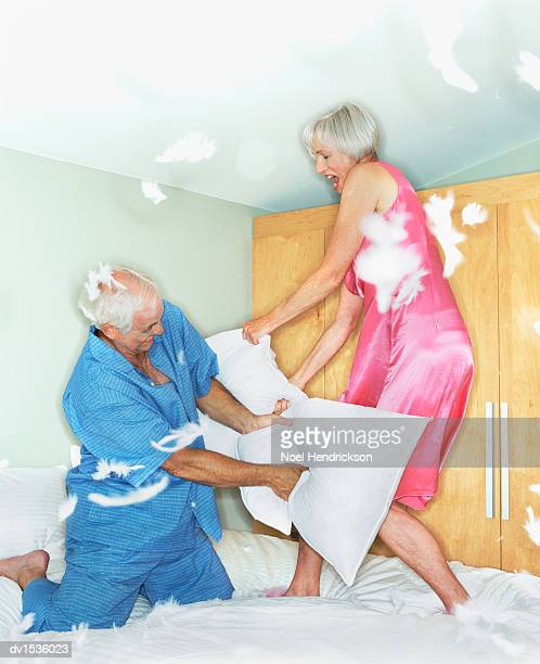 Elderly Couple Having a Pillow Fight on a Bed, Feathers in Mid-Air