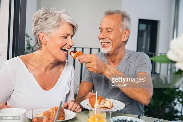 Elderly couple having breakfast at balcony