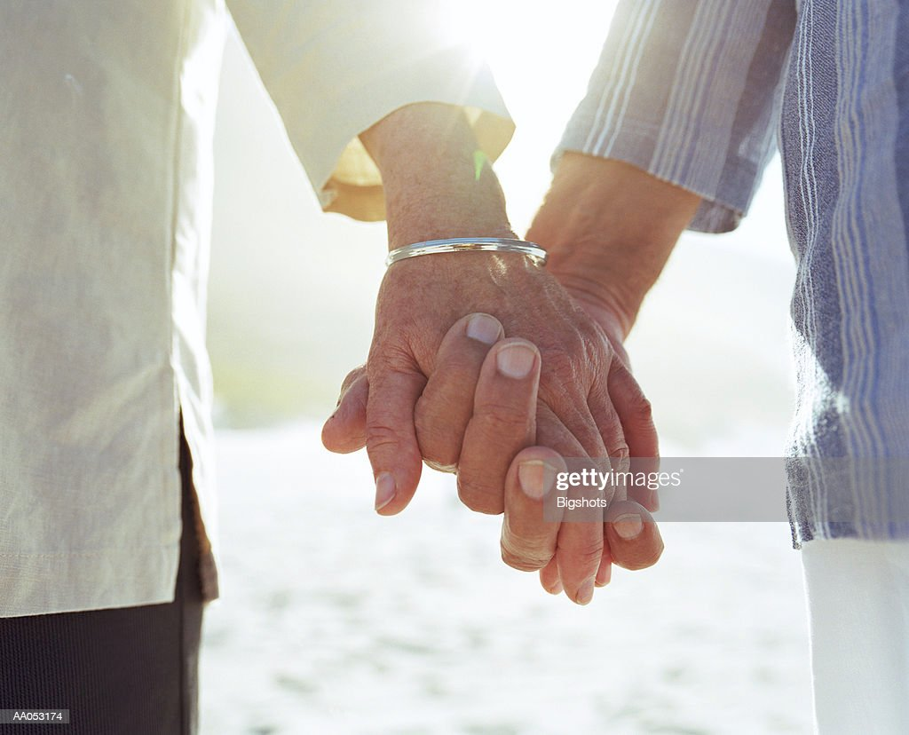 Elderly couple holding hands, close-up of hands : Stockfoto