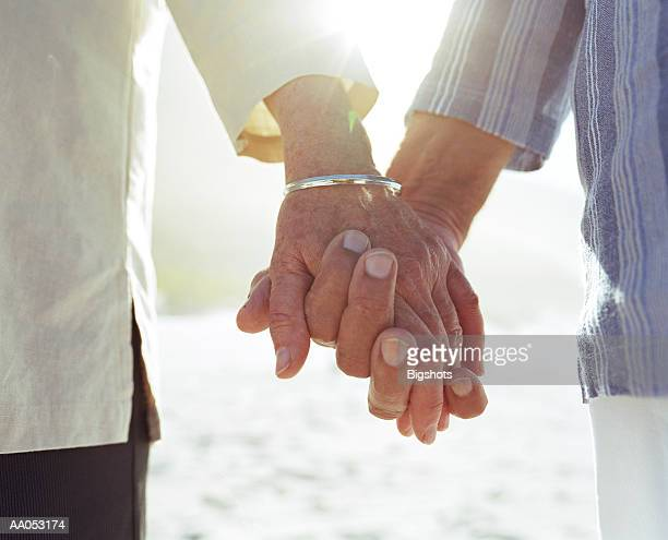 Elderly couple holding hands, close-up of hands