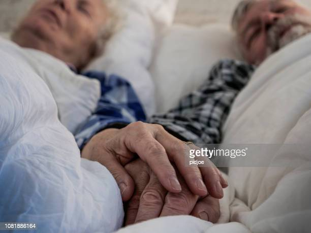 elderly couple holding hands in bed - wrinkled stock pictures, royalty-free photos & images