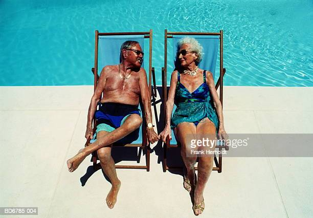 Elderly couple in deckchairs by pool, elevated view