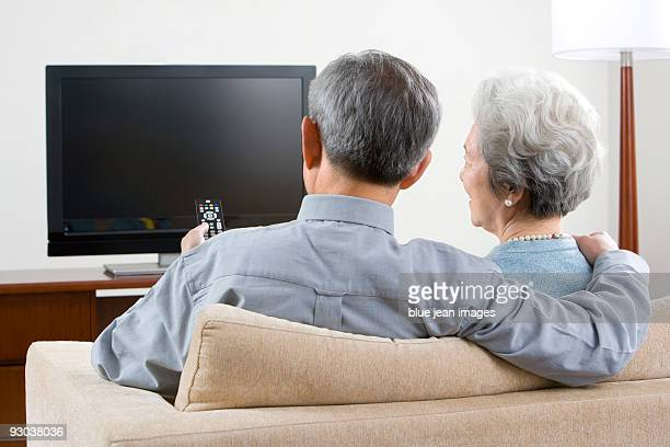 Elderly couple in front of widescreen television