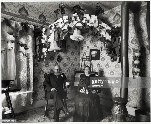 Elderly couple in room decked out with what seems to be decorations for a golden wedding anniversary Photograph by W A Raymond ca 1900 in Oregon