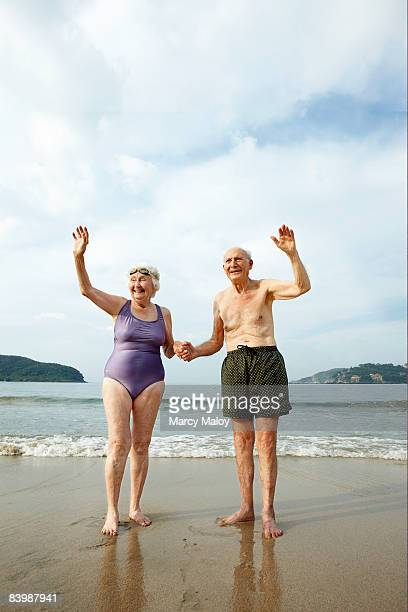 Elderly couple in swimsuits waving on the beach.