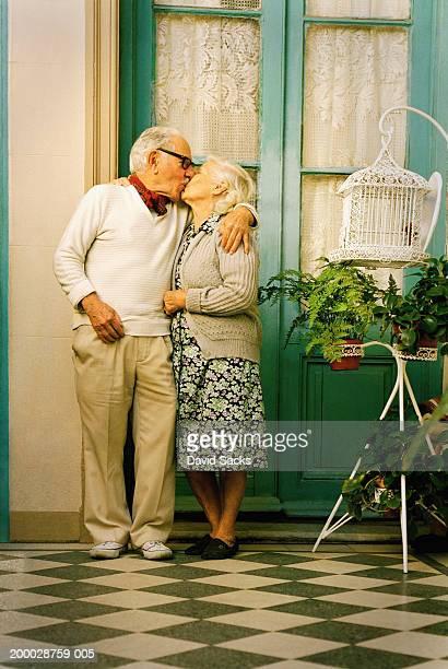 Elderly couple kissing outside house