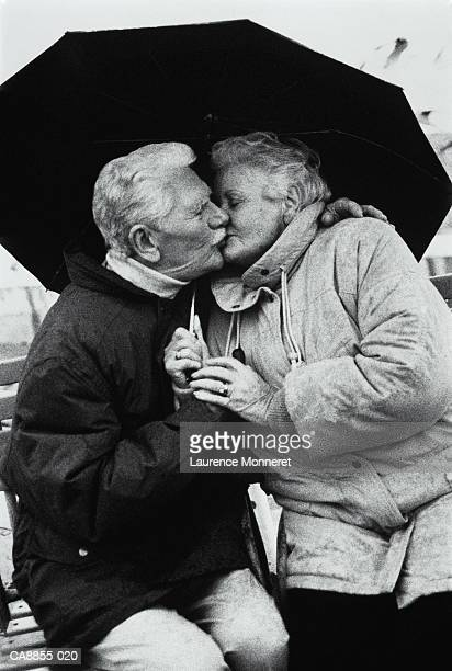 Elderly couple kissing under umbrella, close-up (B&W)