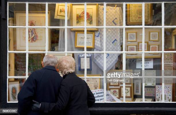 Elderly couple look in the window of a haberdashery shop Burford Oxfordshire UK