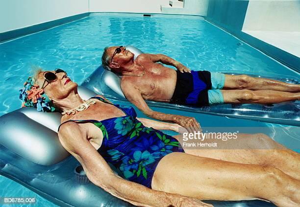 elderly couple lying on inflatables in pool - coup de soleil photos et images de collection