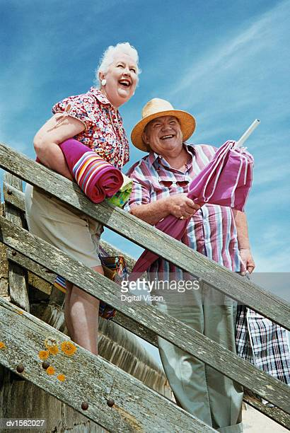 Elderly Couple on Holiday Standing on Steps to a Beach