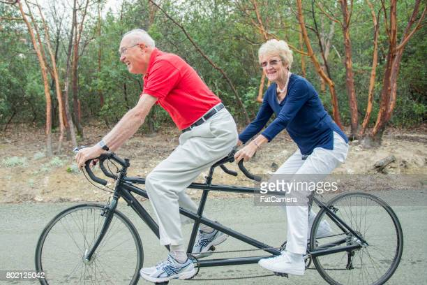 elderly couple on tandem bike - tandem bicycle stock pictures, royalty-free photos & images