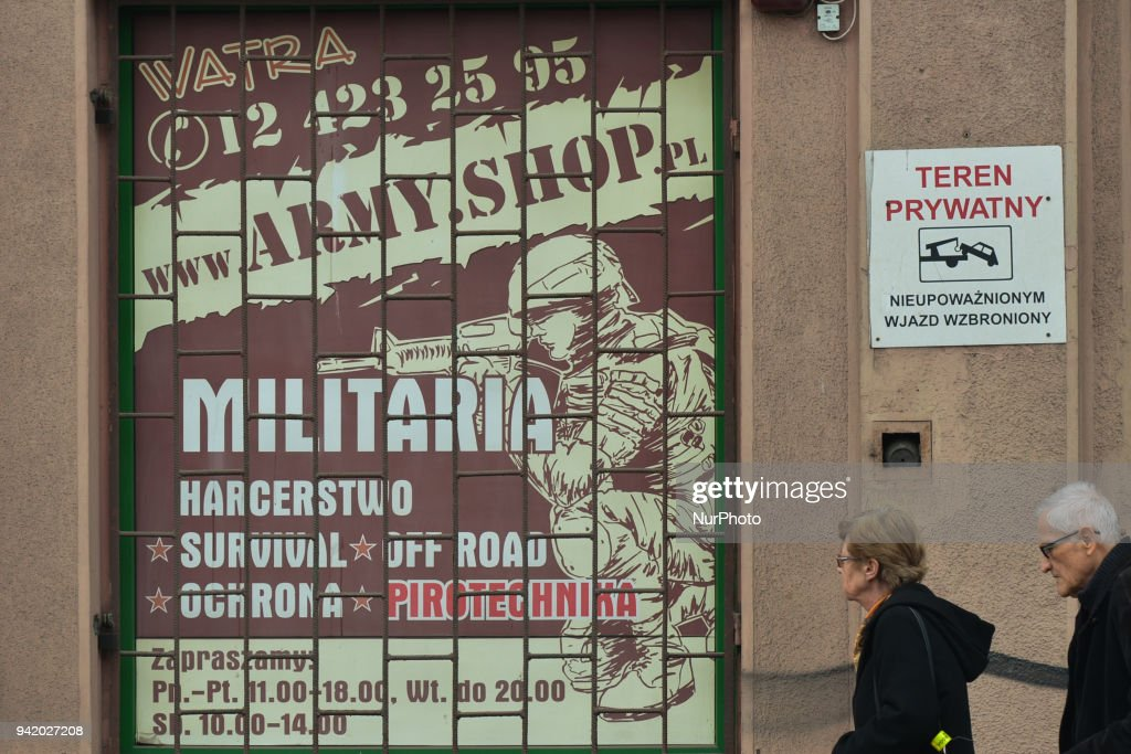 A elderly couple passes by 'Militaria' shop window in Krakow's city