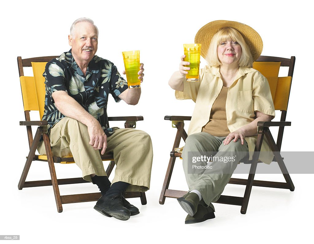 Elderly couple relax together sitting and enjoying a cold drink. : Foto de stock
