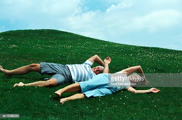 elderly couple rolling down a hill - lying down photos et images de collection