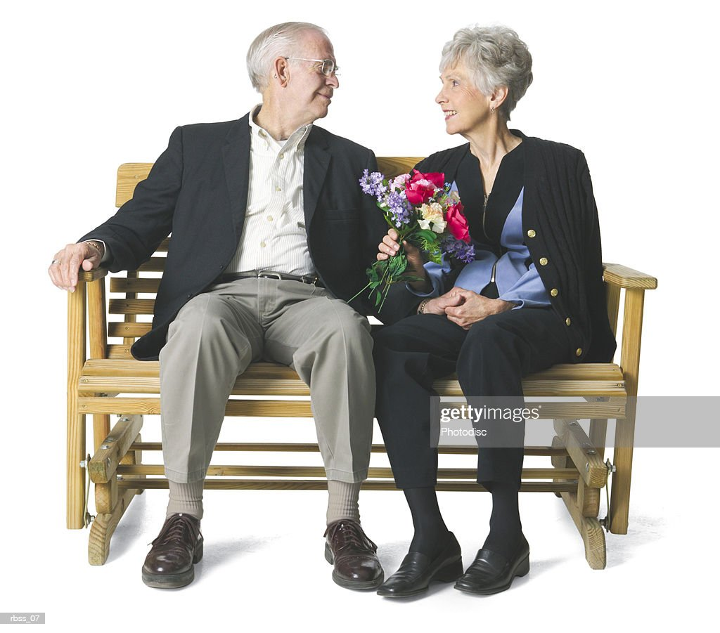 Elderly couple sit on a bench and gaze lovingly into each others eyes. : Stock Photo