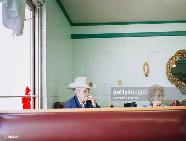 elderly couple sitting in a diner. - diner stock pictures, royalty-free photos & images