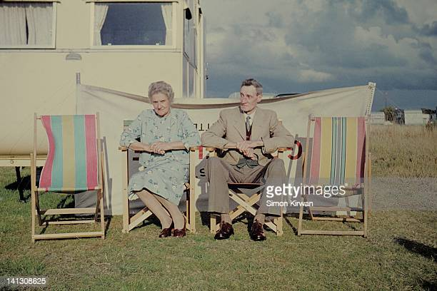 Elderly couple sitting in deckchairs