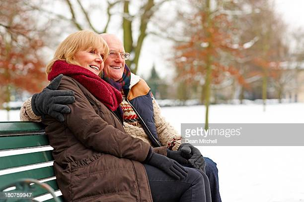 Elderly couple sitting on a bench at snow park