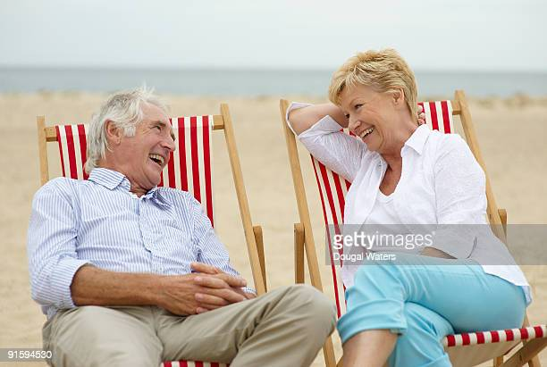 Elderly couple sitting together at beach.
