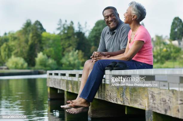 elderly couple sitting together on a pier - african american couple stock pictures, royalty-free photos & images