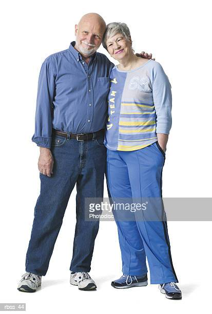 Elderly couple smile as they lean together.