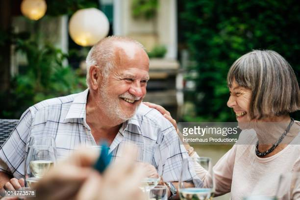 elderly couple smiling at family bbq - terceira idade - fotografias e filmes do acervo