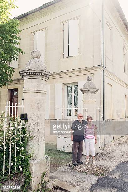 Elderly couple standing in front of their house in summer.