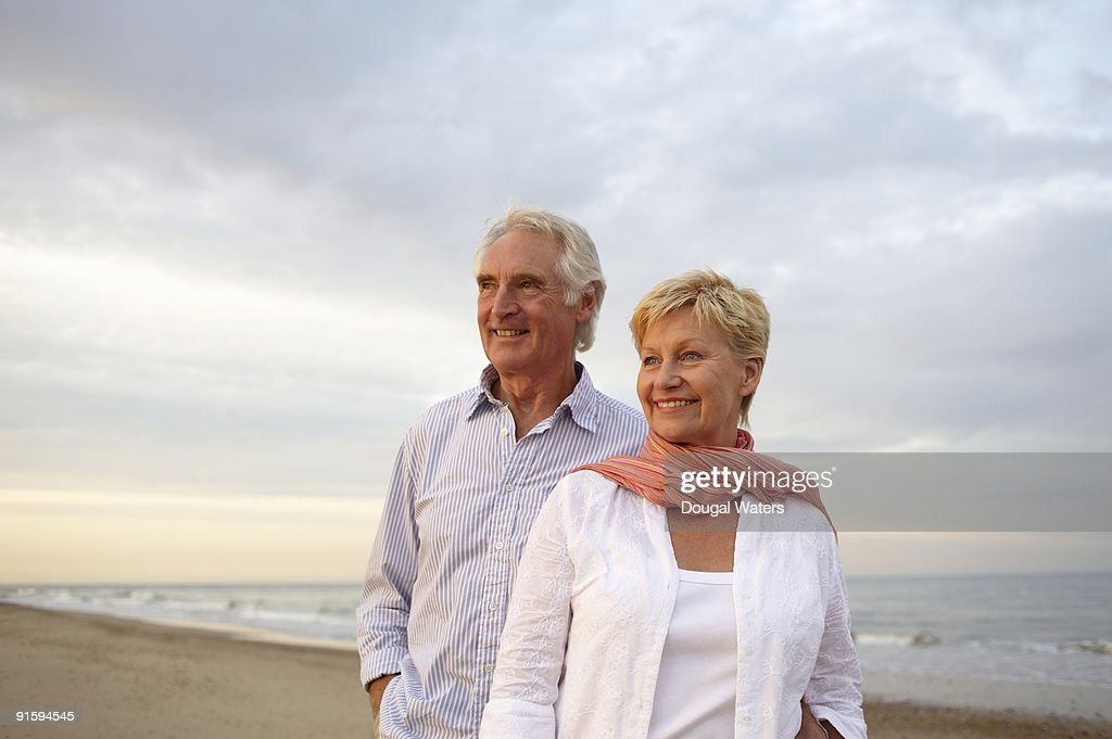 Elderly couple standing together at beach. : Foto stock