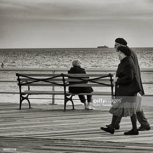 Elderly couple strolls along the boardwalk on a cold autumn day, Coney Island, NY, November 2011