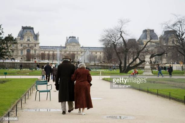Elderly couple take a calm stroll arm in arm through Jardin des Tuileries by the Louvre Museum art gallery Central Paris France