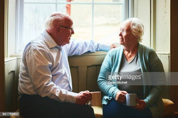 Elderly couple talking while relaxing by a window