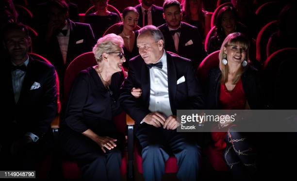 elderly couple talking while sitting in theater - evening wear stock pictures, royalty-free photos & images