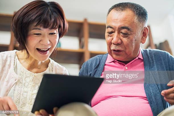 年配のカップルデジタルタブレットを使用しております。