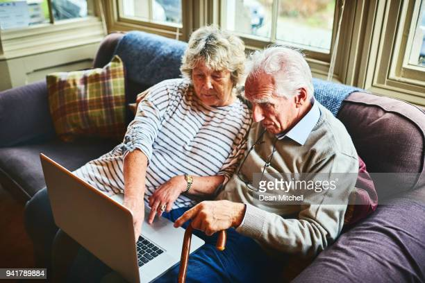Elderly couple using laptop computer together at home