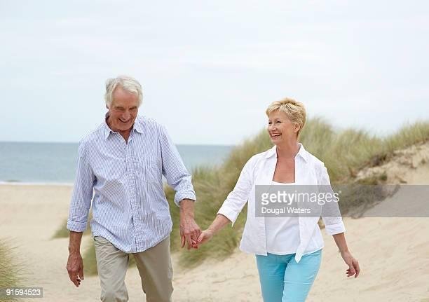 Elderly couple walking at beach.