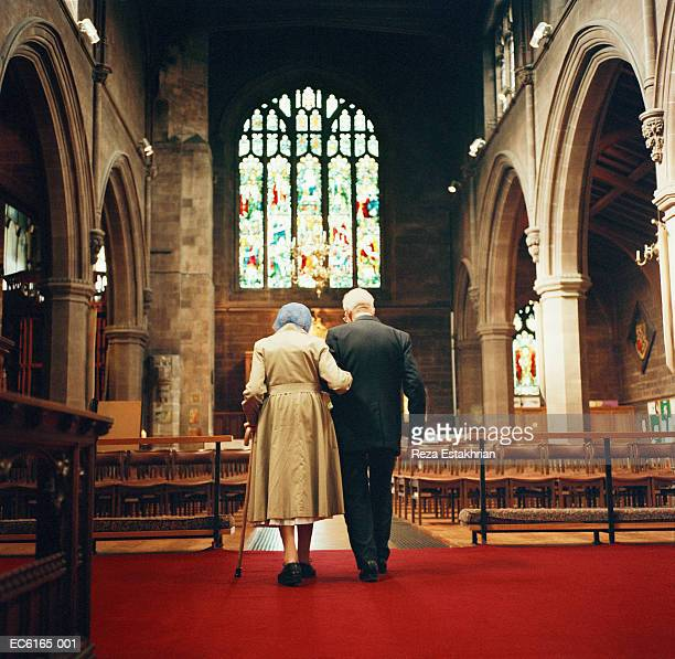 elderly couple walking down aisle of church away from altar - 一張羅 ストックフォトと画像