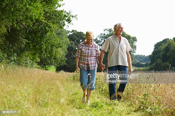 Elderly couple walking in countryside.
