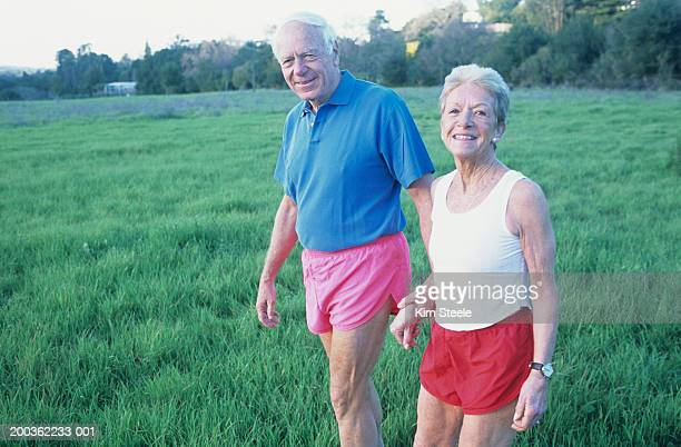 Elderly couple walking in countryside, Portrait