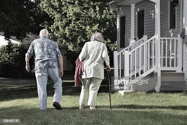 Elderly Couple Walking Slowly Together in Back Yard
