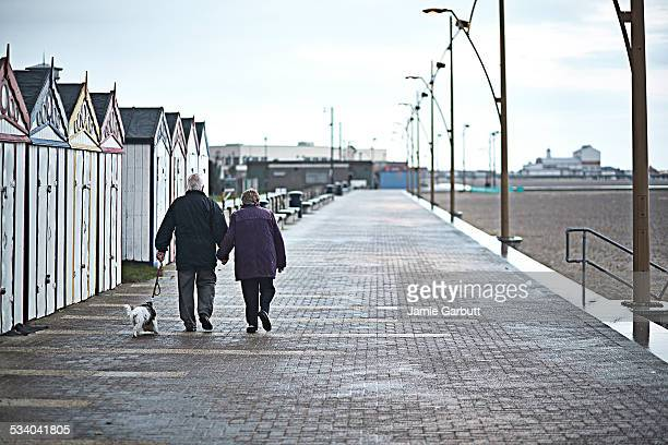 elderly couple walking together in the rain - beach hut stock pictures, royalty-free photos & images