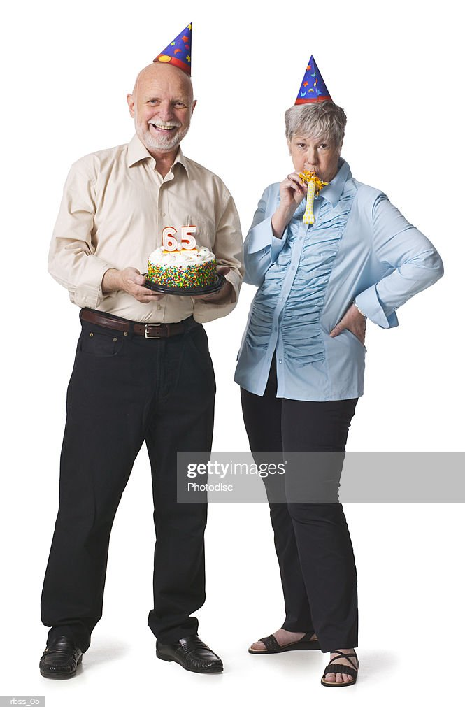 Elderly couple with party hats and birthday cake celebrate a birthday. : Foto de stock