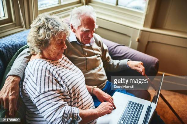 Elderly couple working on a laptop at home