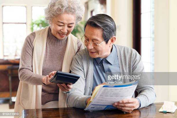 elderly couples are managing finances - fun calculator stock photos and pictures