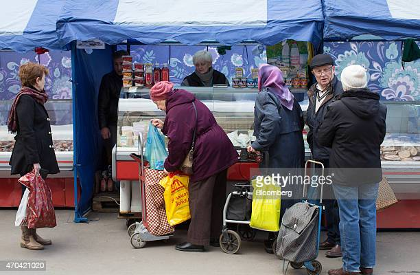 Elderly customers queue at a delicatessen open air street market stall in Moscow Russia on Saturday April 18 2015 Russia will extend a freeze on...